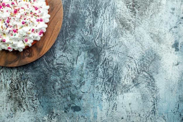 Ansicht der oberen hälfte kuchen mit gebäckcreme auf schneidebrett auf grauem tisch