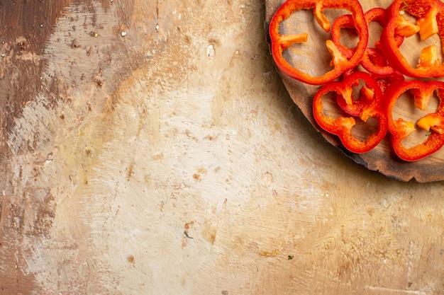 Ansicht der oberen hälfte rote paprika in stücke geschnitten auf rundem baumholzbrett auf bernsteinfarbenem hintergrund