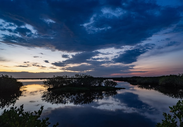 Ansicht der reflexion des himmels im see mit mangroven in floridas weltraumküste bei sonnenaufgang