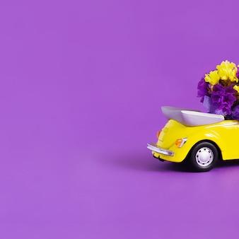 Ansicht der rückseite des kofferraums eines leuchtend gelben cabrioautos mit einem blumenstrauß auf einem purpur. konzept urlaub, lieferung, kunst, transport