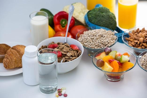 Ansicht der schüssel getreide, pillen und lebensmittels auf einer weißen tabelle