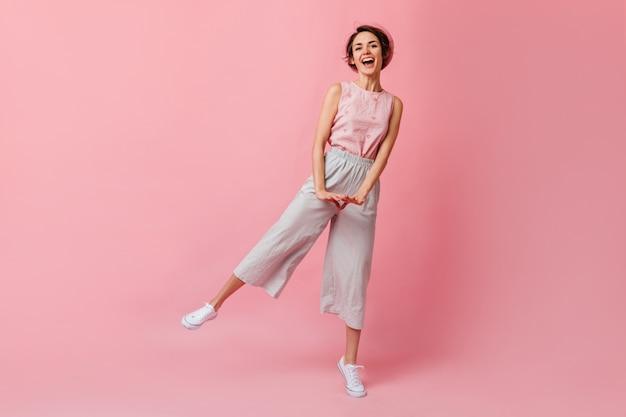 Ansicht der tanzenden frau in voller länge in der rosa baskenmütze