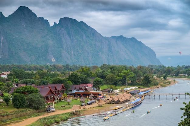 Ansicht der touristischen boote auf dem nam song river- und gebirgshintergrund