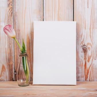 Ansicht der tulpenblume im vase mit schwarzem plakat auf hölzernem hintergrund