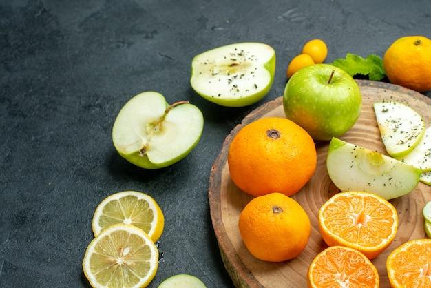 Ansicht der unteren hälfte geschnittene äpfel und mandarinen auf rustikalem servierbrett geschnittene zitronenscheiben auf dunklem tisch