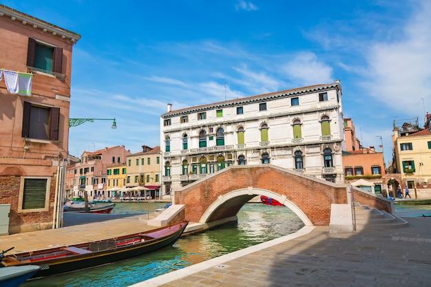Ansicht der venedig-straße und -kanals mit booten und der kleinen brücke am sonnigen tag venedigs, italien.