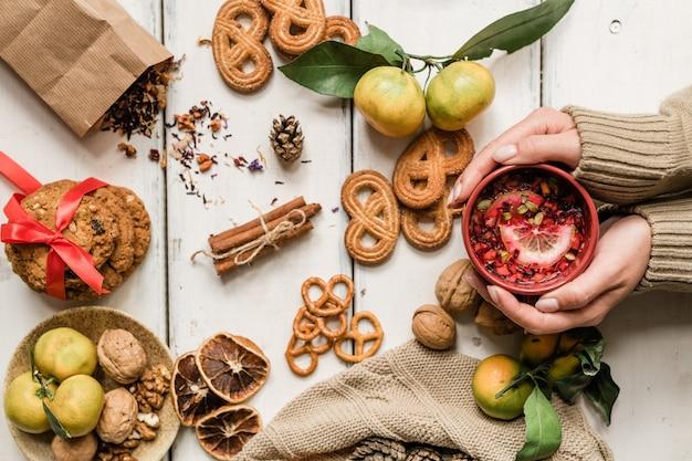 Ansicht der weiblichen hände, die becher mit heißem getränk unter hausgemachten keksen, walnüssen, clementinen und gewürzen auf weißem tisch halten