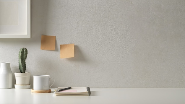 Ansicht des arbeitsbereichs im arbeitszimmer mit kopierraum, briefpapier, blumentopf und dekorationen