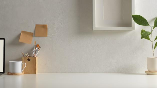 Ansicht des arbeitsbereichs im home-office-raum mit kopierraum, laptop, zubehör und dekorationen