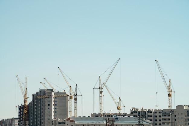 Ansicht des aufbaus der nahaufnahme. gruppe von mehrfamilienhäusern im bau. viele kräne in arbeit. kleine baumeister auf gebäudedächern. stadtbild mit kränen, gebäuden und arbeitern.