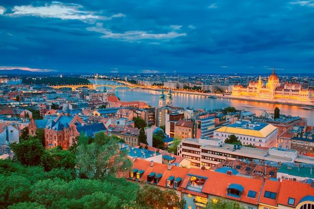 Ansicht des beleuchteten parlaments und des flussufers der donau in budapest, ungarn während des sonnenuntergangs mit dramatischem himmel.