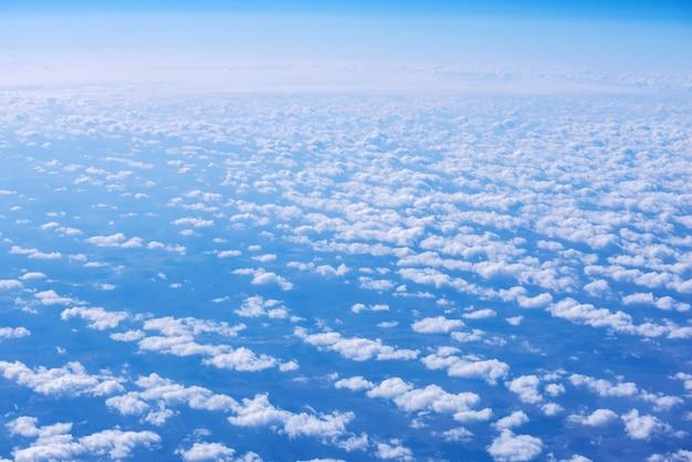 Ansicht des blauen himmels über den wolken vom flugzeugfenster
