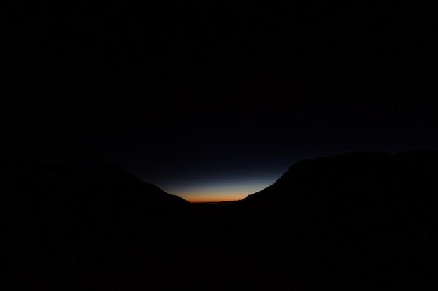 Ansicht des dunklen schattenbildhügels in der nacht mit einem licht auf ihnen