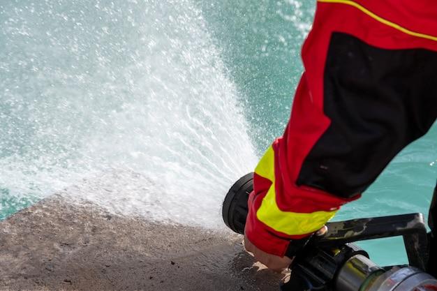Ansicht des feuerwehrmanns, der den wasserschlauch reguliert