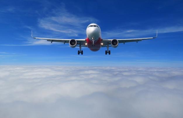 Ansicht des flugzeuges mit der vollen landungskonfiguration, die über die schöne wolke fliegt.