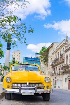 Ansicht des gelben klassischen weinleseautos in altem havana, kuba