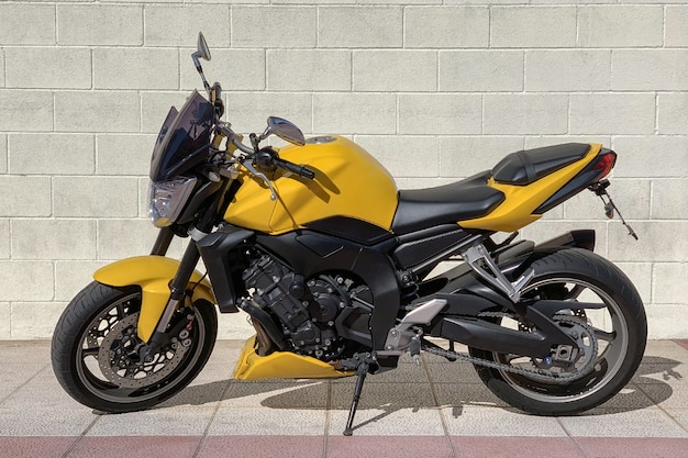 Ansicht des gelben sportmotorrads der backsteinmauer