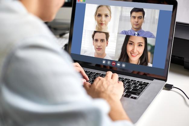Ansicht des hinteren mannes, der laptop-videokonferenz verwendet und mit kollegen arbeitet