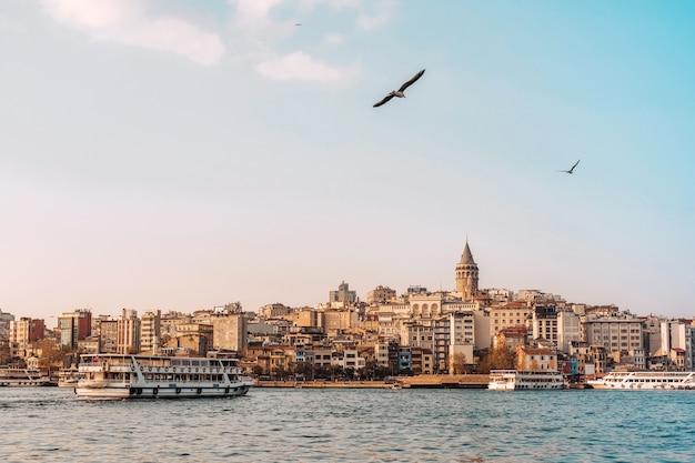 Ansicht des istanbuler stadtbildes galata tower mit schwimmenden touristenbooten im bosporus, istanbul türkei