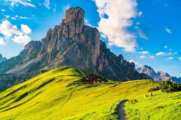 Ansicht des italienischen dolomitberges bei giau pass am abend mit dem hügel von gelben blumen und von italienischem haus in belluno, italien.