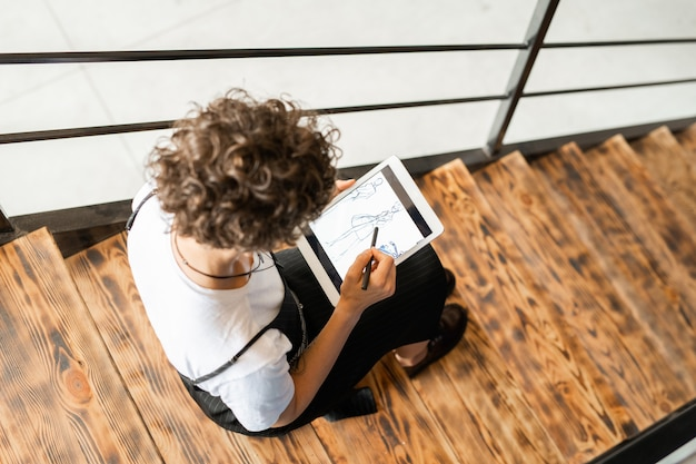 Ansicht des jungen eleganten modedesigners, der auf eine der neuen skizzen zeigt, die auf digitalem tablett angezeigt werden, während über neuer sammlung gearbeitet wird
