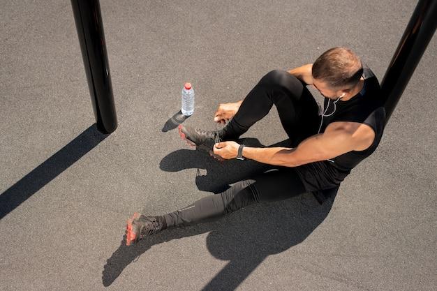 Ansicht des jungen sportlers, der auf sportplatz im freien sitzt und schnürsenkel des turnschuhs vor dem training bindet