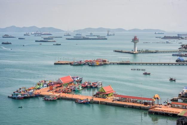 Ansicht des ko sichang leuchtturms und des hafens mit transportschiff und lokalem boot mit schönem meer der ostküste thailands.
