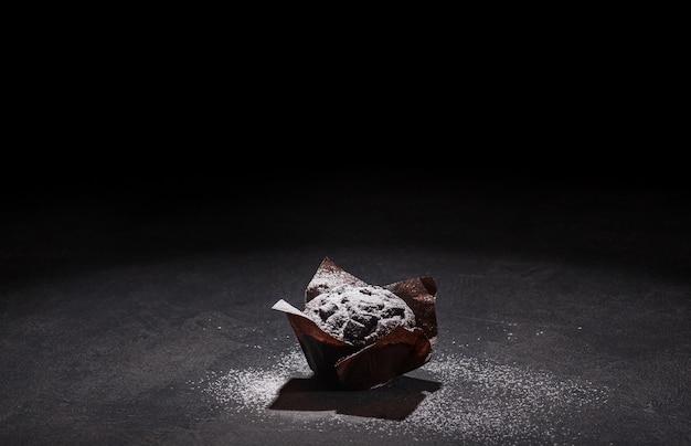 Ansicht des köstlichen schokoladenmuffins bedeckt von puderzucker