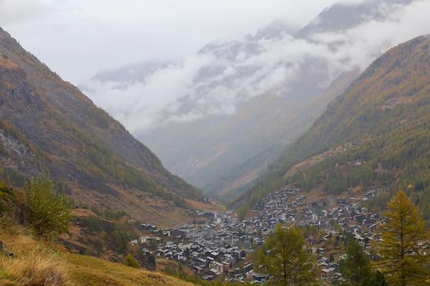 Ansicht des landschaftsbaumberges und des dorfes in der herbstnatur und -umgebung bei schweizer