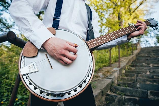 Ansicht des musikers, der banjo an der straße spielt