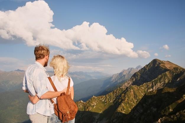 Ansicht des paares, das den sonnenuntergang auf die oberseite des berges aufpasst