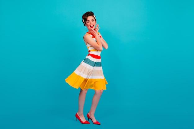 Ansicht des pinup-mädchens in gestreifter kleidung in voller länge. studioaufnahme der brünetten dame, die auf blauem hintergrund tanzt.