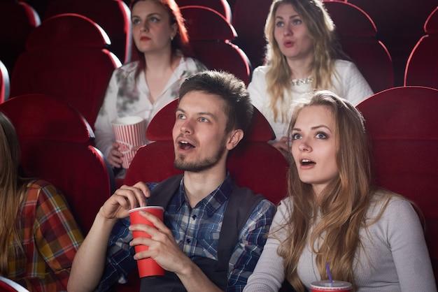 Ansicht des schockierten paares, das bildschirm im kino mit geöffnetem mund betrachtet. hübsches blondes mädchen im grauen und gutaussehenden mann, der gruselfilm genießt. konzept von freunden und freizeit.
