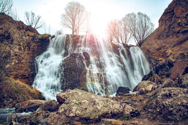 Ansicht des schönen bergwasserfalls mit blauem himmel auf hintergrund