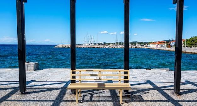 Ansicht des seehafens mit festgemachten yachten, ägäisches meer, ansicht von einem pavillon auf einem pier mit schwarzen metallpfosten und einer bank in nikiti, griechenland