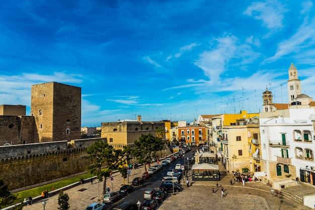 Ansicht des svevo schlosses und des quadrats von federico ii di svevia ein frühlingstag mit einem hintergrund des blauen himmels und der wolken.
