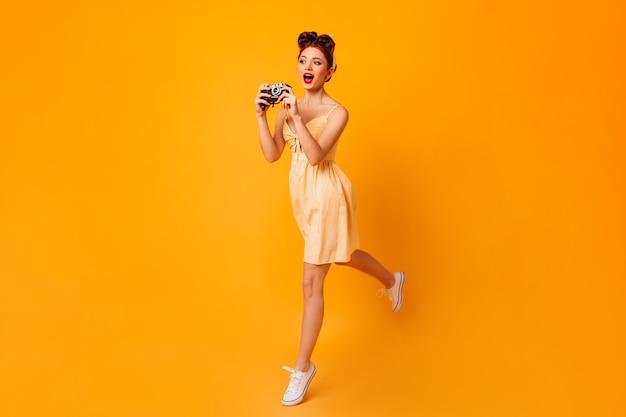 Ansicht des tanzenden fotografen in voller länge. studioaufnahme des pinup-mädchens, das mit kamera springt.