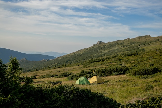 Ansicht des touristenzeltes in den bergen bei sonnenaufgang oder sonnenuntergang. camping. abenteuerreise konzept für aktiven lebensstil freiheit. sommerurlaub.