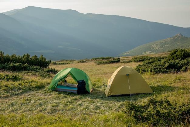 Ansicht des touristenzeltes in den bergen bei sonnenaufgang oder sonnenuntergang. camping hintergrund