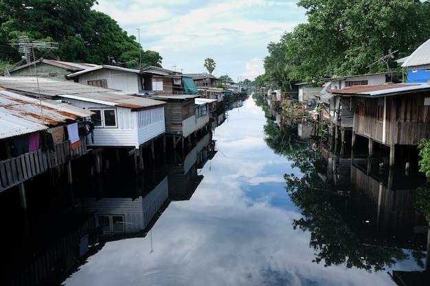 Ansicht des verschmutzten kanals des elendsviertels in der nähe mit blauem himmel