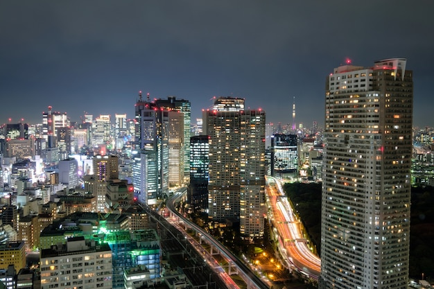 Ansicht des wolkenkratzers und des glühenden hellen verkehrs herein in die stadt nachts