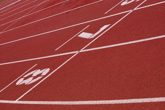 Ansicht einer athletischen laufbahn des roten tartan mit weißen zahlen.