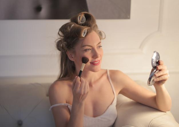 Ansicht einer frau, die make-up mit bigudies im haar und einem kleinen spiegel in der hand tut