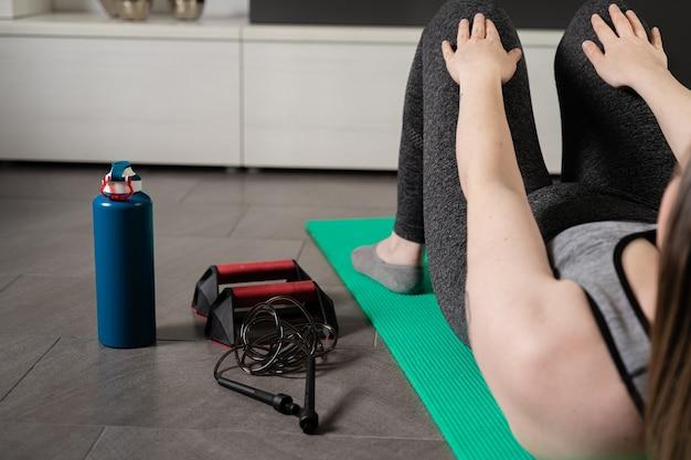 Ansicht einer jungen frau auf ihrem rücken, die sit-ups mit den sportgeräten neben ihr macht.