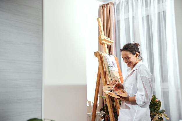 Ansicht einer schönen malerin mit gesammelten haaren in einem brötchen und pinseln in ihren haaren, die vor der staffelei in werkstatt und zeichnung stehen