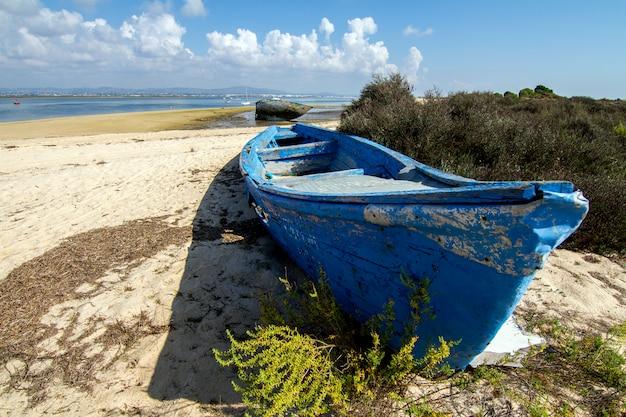 Ansicht eines alten verlassenen bootes gestrandet auf trockenem sand am strand.