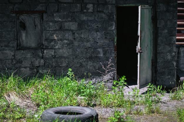 Ansicht eines alten verlassenen gebäudes, das oben das fenster verschalt und im sommer die tür öffnet.
