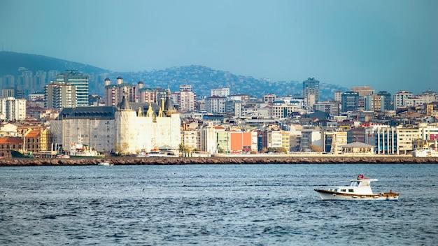 Ansicht eines bezirks mit wohngebäuden und hochmodernen gebäuden in istanbul, bosporus-straße mit beweglichem boot auf dem vordergrund, türkei