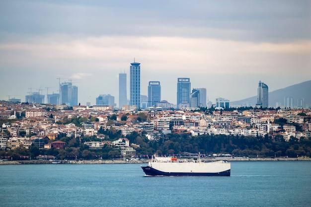Ansicht eines bezirks mit wohngebäuden und hochmodernen gebäuden in istanbul, bosporus-straße mit beweglichem schiff im vordergrund, türkei