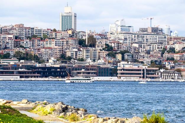 Ansicht eines bezirks mit wohngebäuden und hochmodernen gebäuden in istanbul, bosporus-straße mit booten, leute, die am ufer ruhen, türkei